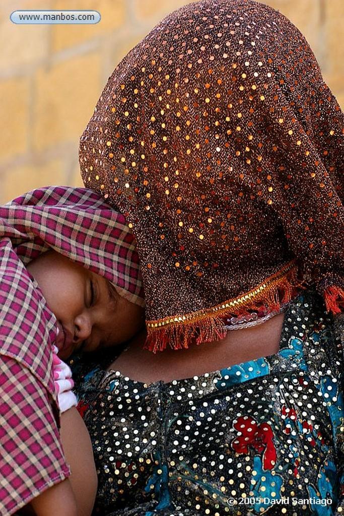 Foto de Jaisalmer, India - Mujer con el rostro tapado llevando a su hijo en Jaisalmer